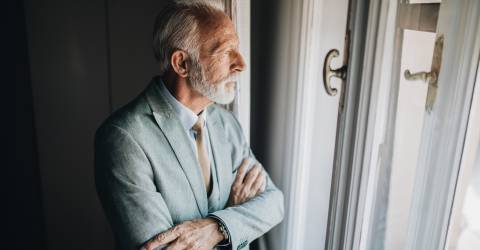 Bezorgd zakenman op zoek door het raam van een appartement